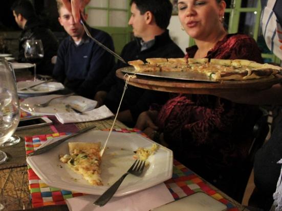 Ara servindo aos gastromalucos sua pizza de pesto, mussarela de búfala e nozes